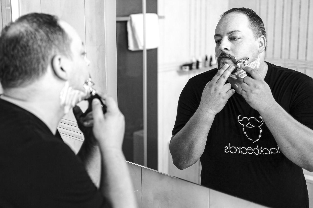 Mann mit Henriquatre, rasiert mit Rasierhobel die Konturen.