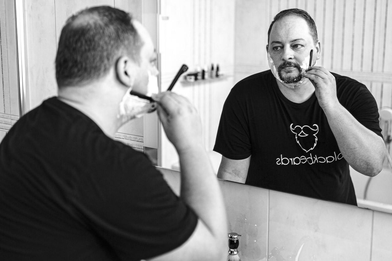 Mann mit Henriquatre, rasiert sich mit einem Wechselklingenmesser die Kontur.