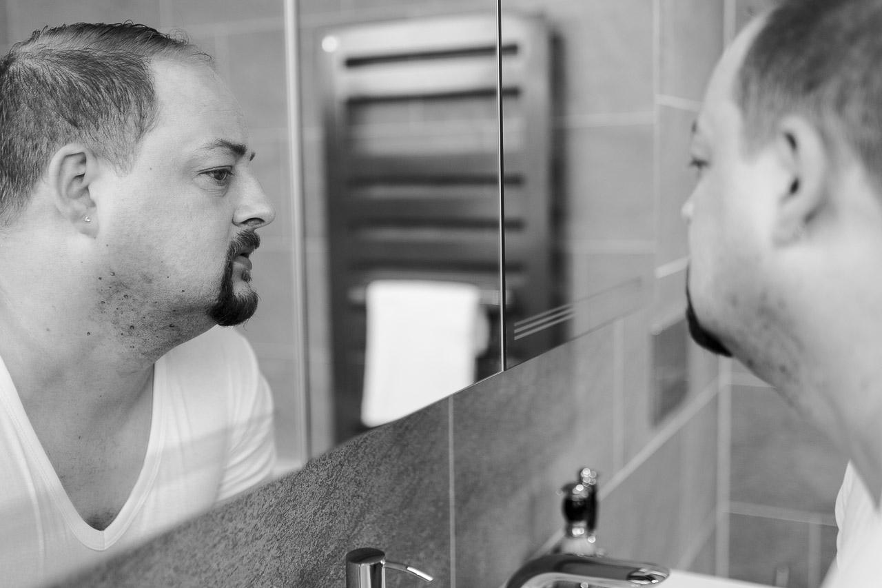Mann mit Henriquatre, schaut in den Spiegel und begutachtet seinen Rasurbrand.