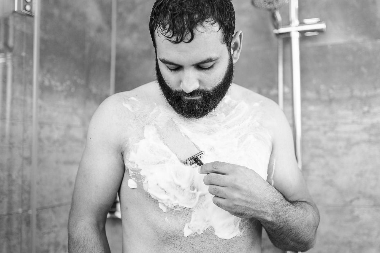 Mann mit Vollbart, rasiert sich die Brust unter der Dusche.