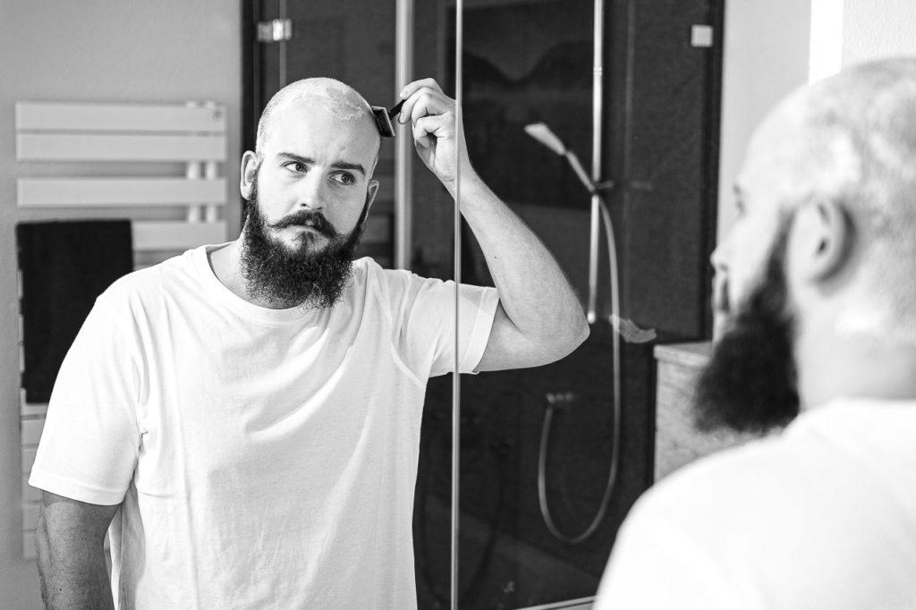 Mann mit Vollbart, rasiert sich seine Glatze, mit einem Rasierhobel.