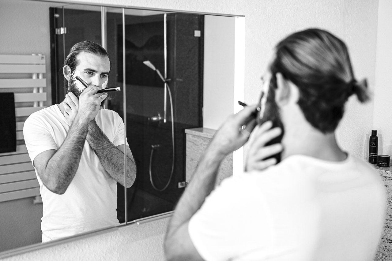 Mann mit Vollbart, rasiert Konturen mit dem Rasiermesser.