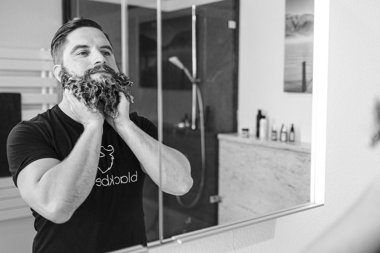 Mann mit Vollbart seift sich den Bart ein.