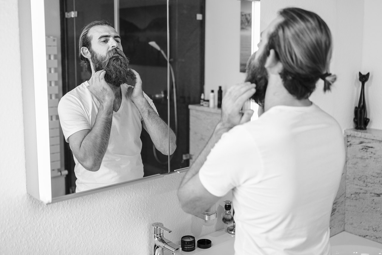 Mann mit Vollbart. streicht mit seinen Händen am Bart.