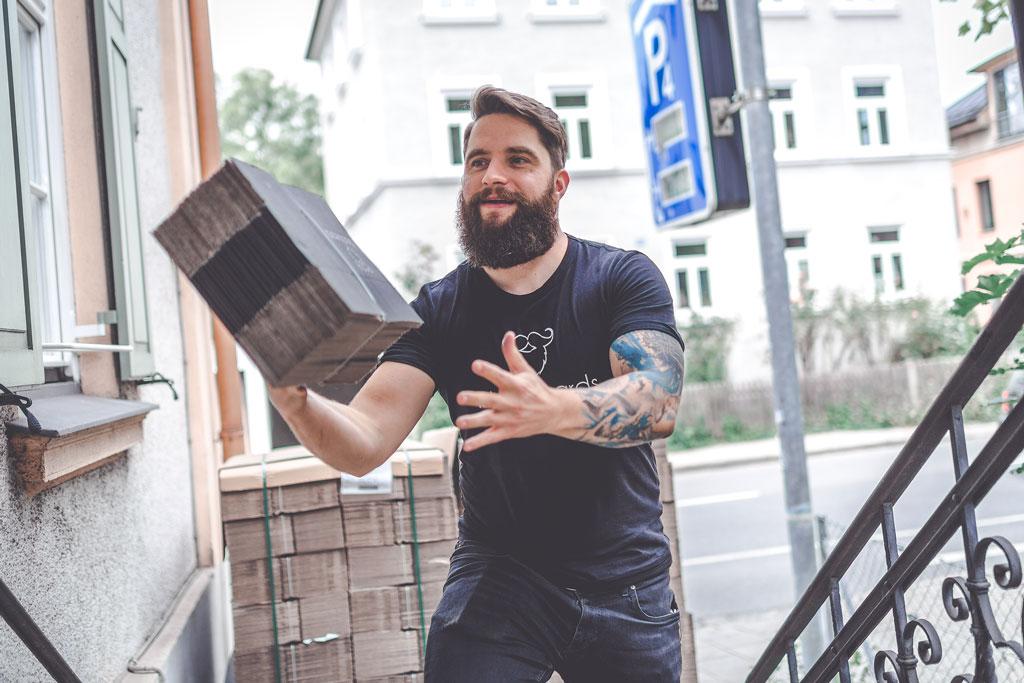 Mann mit Vollbart hat Kartons in der Hand