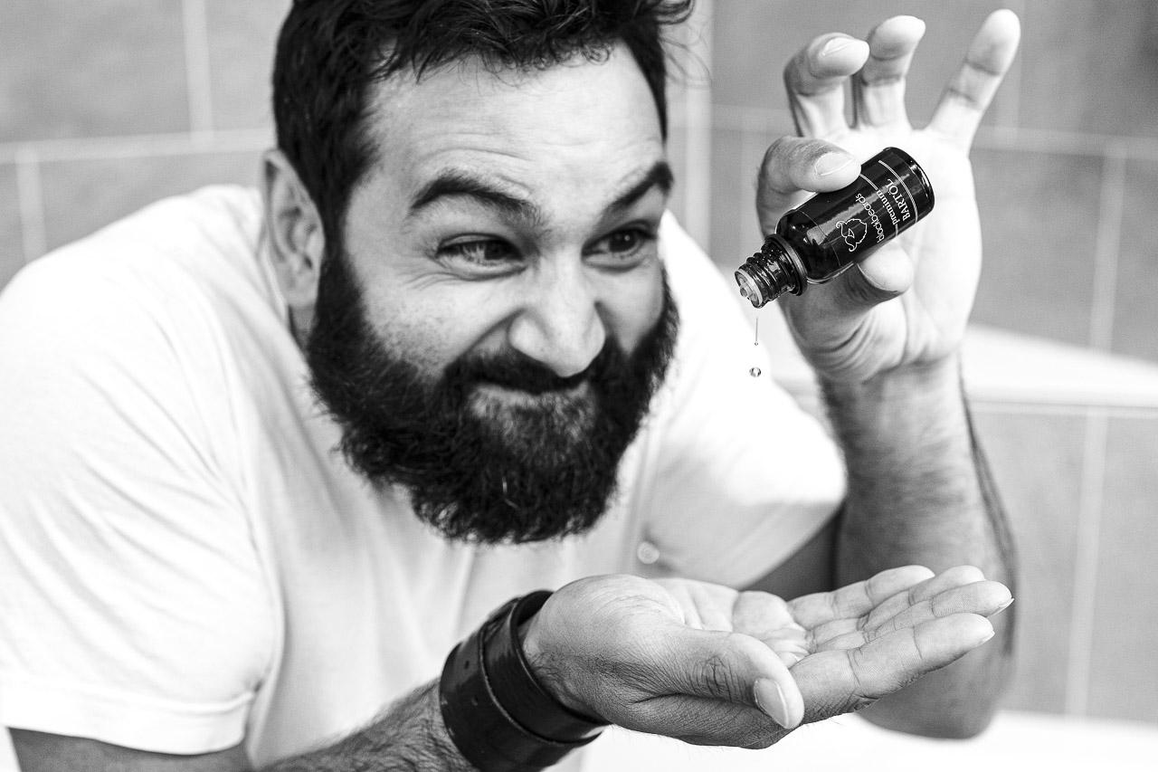 Mann mit zersausten Vollbart, tropft Bartöl in seine Hand.