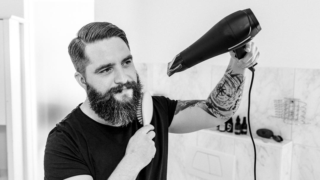 Mike föhnt seinen Bart und bürstet ihn.