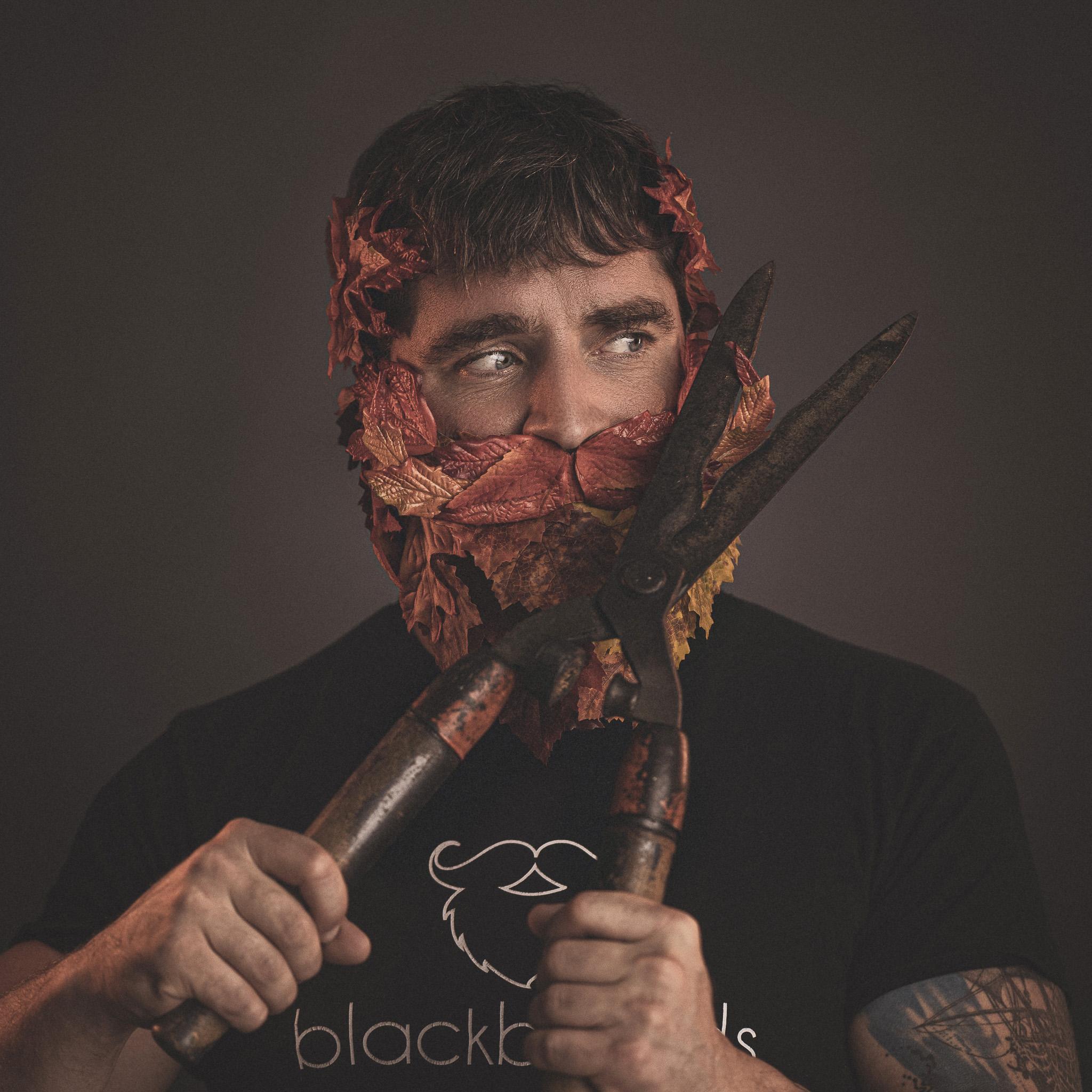 Ein Mann mit einem Bart aus Laubblättern stutzt sich mit einer Heckenschere den Oberlippenbart.
