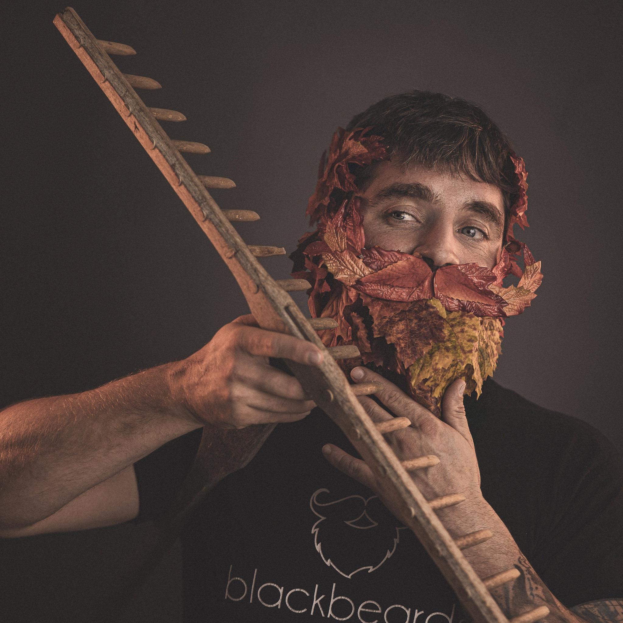 Ein Mann mit einem Bart aus Laubblättern recht seinen Bart mit einem großen Rechen.